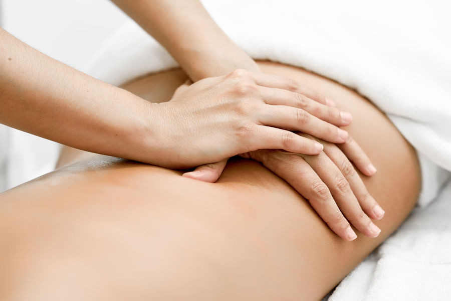 Young woman receiving a back massage in a spa center. Female patient is receiving treatment by professional therapist. Woman Back Massage Female Massage Massage Therapy Physiotherapy Spa Center Young Adult Young Women
