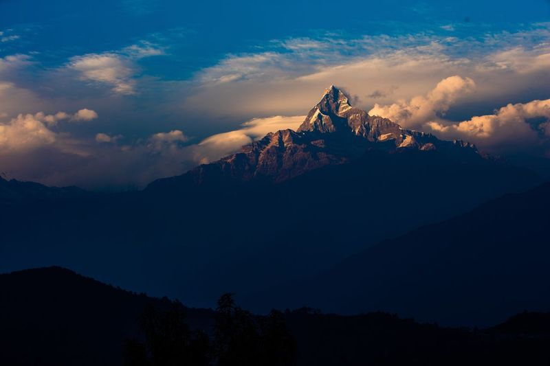 Scenic View Of Mountain Peak Against Sky At Sunset
