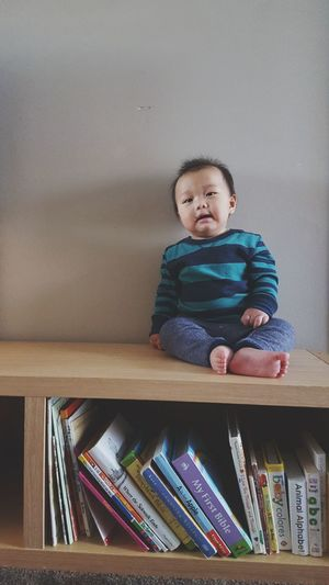 Cute baby boy sitting on bookshelf against wall at home