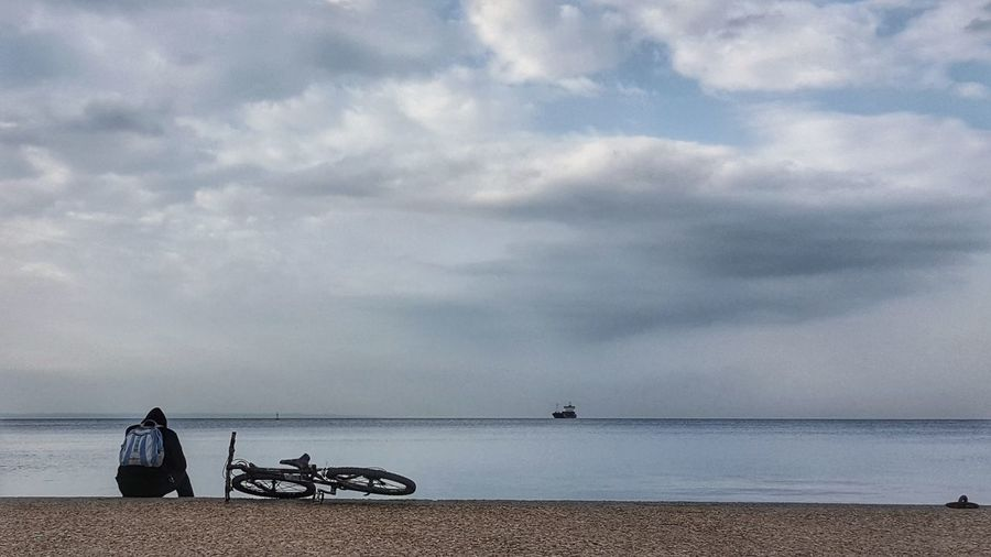 Rear View Of Man Sitting By Bicycle Against Sea