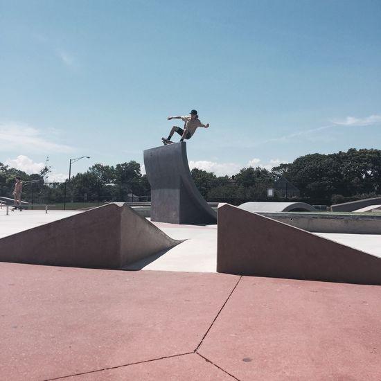 Young Man Performing Stunt At Skateboard Park