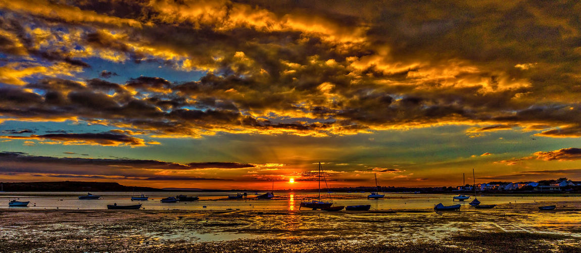 Sunset over Christchurch Harbour Beauty In Nature Christchurch Harbour Cloud Cloud - Sky Cloudy Dramatic Sky Idyllic Mudeford Quay Nature Non-urban Scene Orange Color Outdoors Scenics Shore Sky Sun Sunset Tranquil Scene Tranquility Water Weather