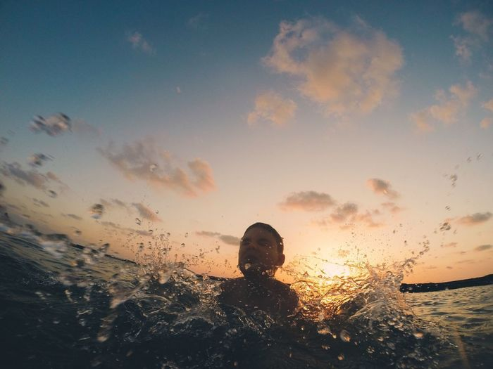 Close-up of boy swimming in sea during sunset