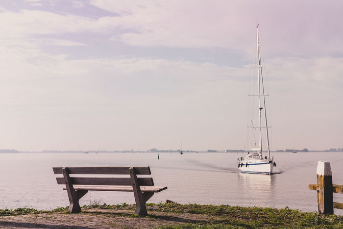 Scenic sea view with bench and sailboat Bay Beauty In Nature Bench Coastline Coastline Landscape Day Horizon Over Water Landscape Nature Nautical Vessel No People Outdoors Relax Sailboat Sailing Scenic Scenics Sea Sky Tranquility Travel View Water Yacht
