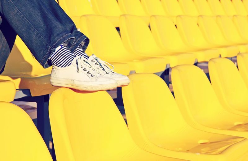 Low section of person on yellow seats at stadium