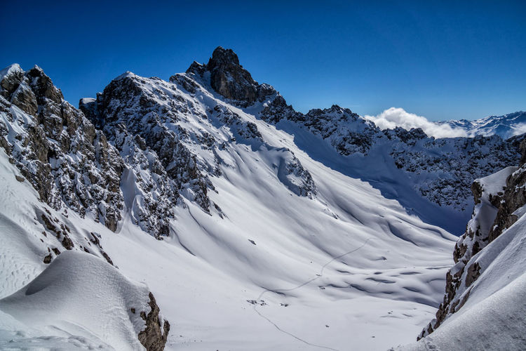 Scenic view of snow covered mountains against clear blue sky