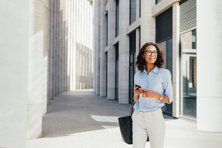 One Person Businesswoman Wireless Technology Business Person Standing Building Exterior Holding Outdoors Beautiful Woman Hairstyle Technology City Built Structure Copy Space Smarthphone Communication Day Eyeglasses  Young Entrepreneur Lifestyles