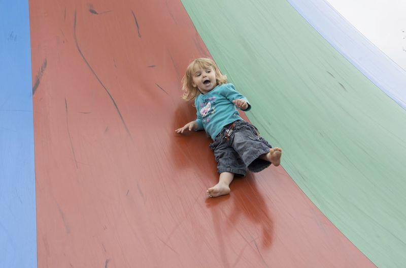 Blond barefoot toddler sliding