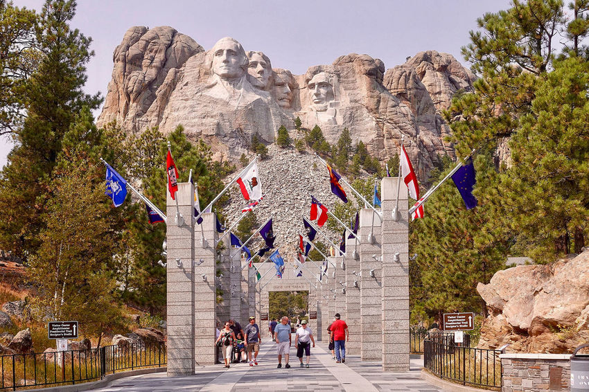The Mount Rushmore National Memorial in the USA. Clear Sky Mount Rushmore National Memorial South Dakota Tourists Trees USA Alley Built Structure Day Flags Mountain Outdoors Pillars Presidents Rocks Sculpture Statue Stones Travel Destinations