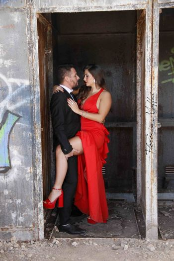 Rear view of couple standing by red wall