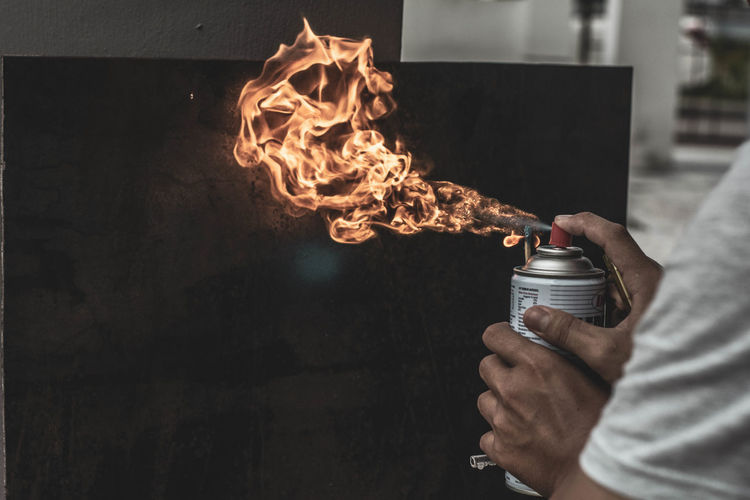 Close-up of man spraying fire on wall with spray bottle