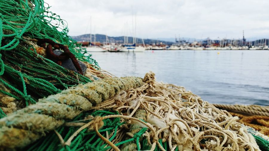 Close-Up Of Fishing Net At Harbor Against Sky