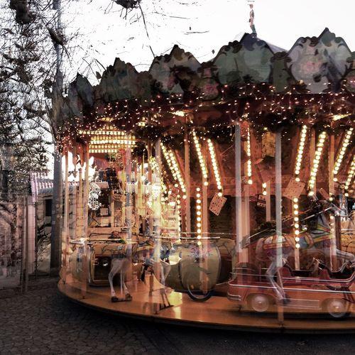 Illuminated carousel against sky at night