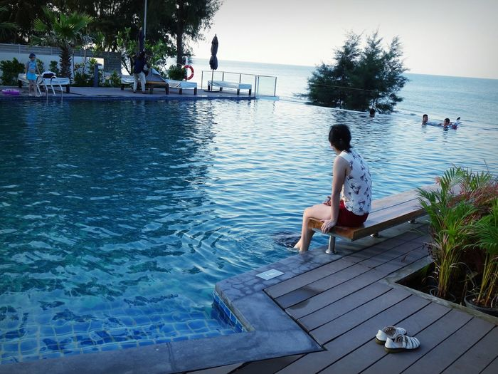 Woman Sitting By Swimming Pool Overlooking The Ocean