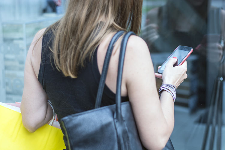 Woman using mobile phone while window shopping in city