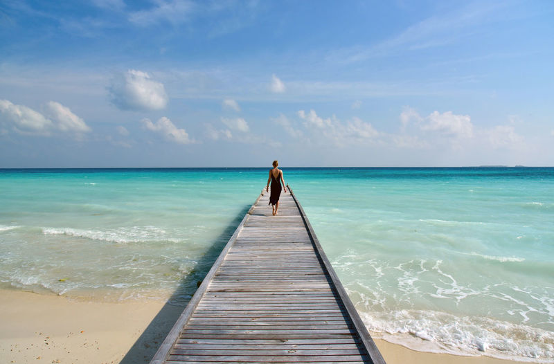 Rear View Of Woman Walking On Pier At Turquoise Sea Against Sky