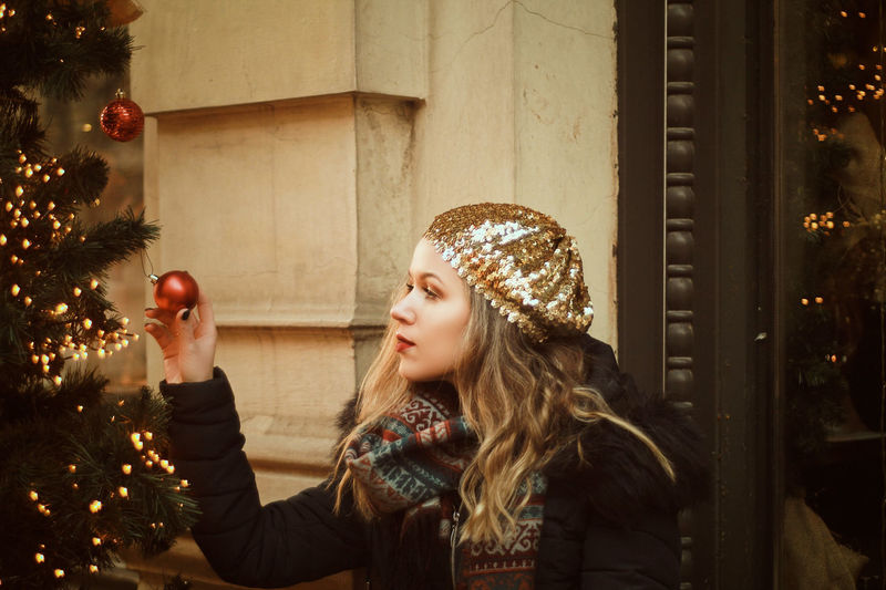 Beautiful woman holding bauble by christmas tree