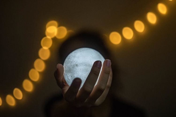 Person holding crystal ball against illuminated lights
