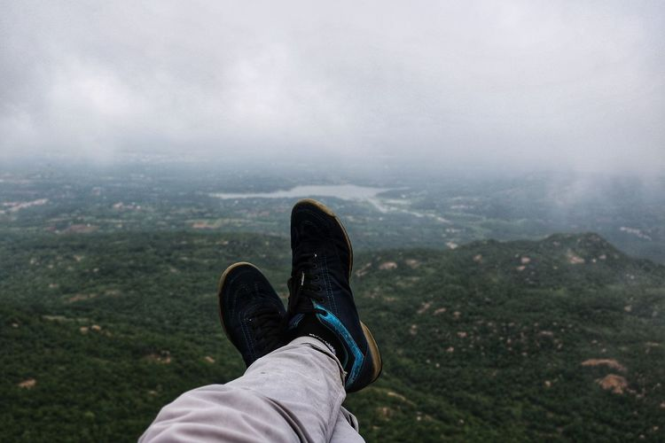 Low section of person on mountain against cloudy sky