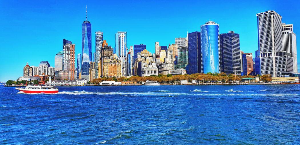 Sea by modern buildings in city against blue sky
