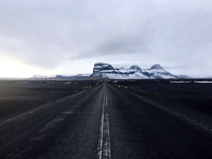 Road Leading Towards Snowcapped Mountain Against Cloudy Sky