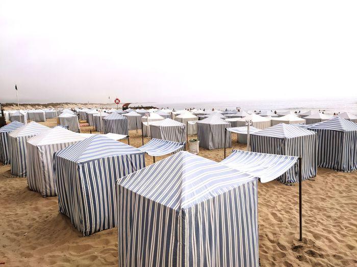 Chairs on beach against clear sky