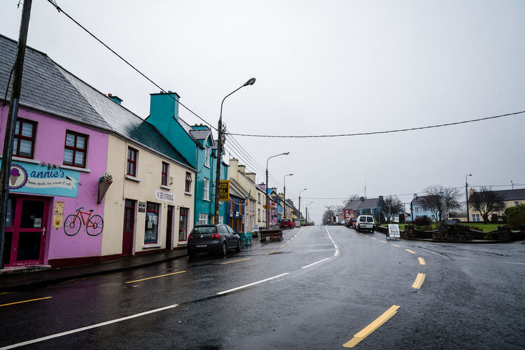 Scenic view of old buildings in Sneem, a small town in the Wild Atlantic Way of Ireland Ireland Pub Road Sneem Travel Wild Atlantic Way Architecture Building Building Exterior Built Structure City Clear Sky Direction Irish Marking Nature No People Outdoors Rain Residential District Restaurant Ring Of Kerry Road Road Marking Sign Sky Street Symbol The Way Forward Transportation Travel Destinations