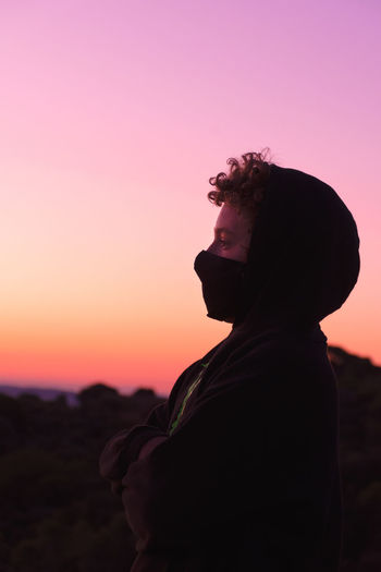 Side view of boy wearing flu mask standing against sky at dusk