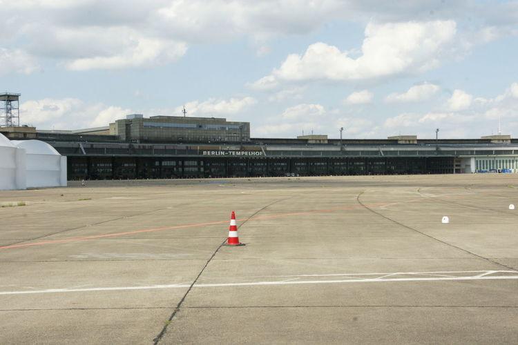 Airplane in airport runway against sky