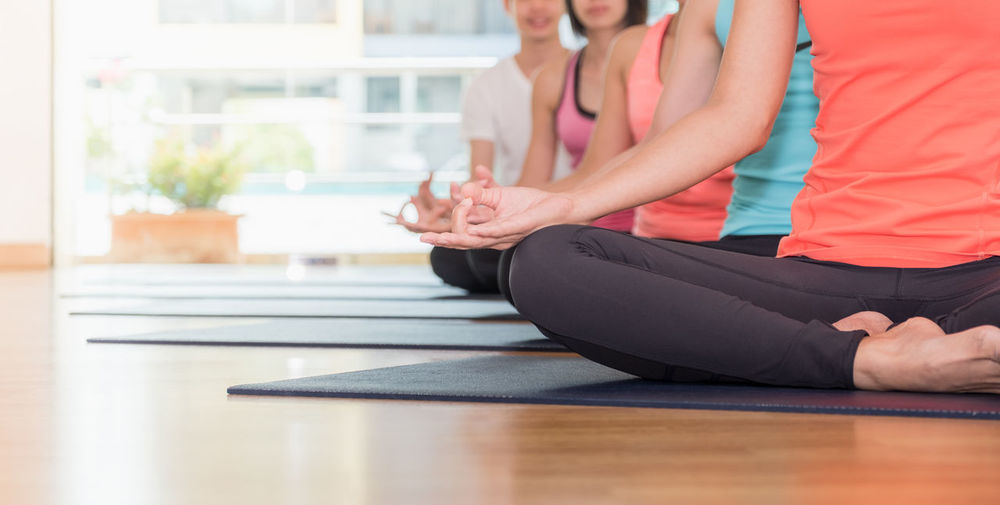 Midsection of women practicing yoga at gym