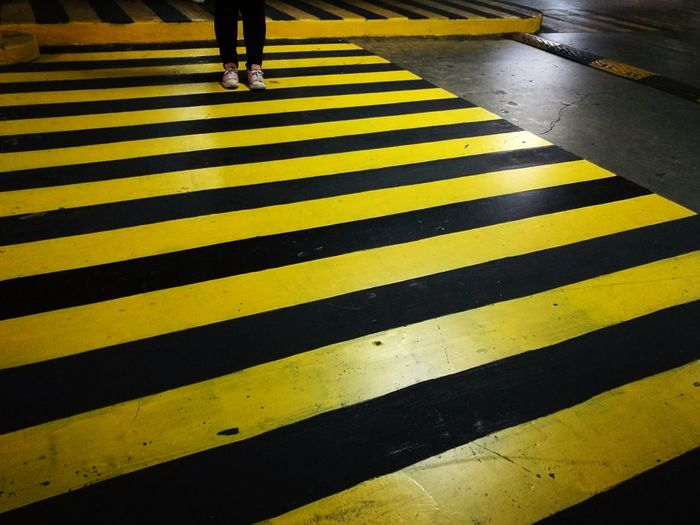 Patterns. Striped Yellow Zebra Crossing Road Marking Street Walking Human Leg Pedestrian City Low Section City Life Human Body Part Road Adult People Zebra Outdoors One Person Day Only Women The Street Photographer - 2017 EyeEm Awards Eyeem Philippines EyeEmNewHere Street Photography Street Art Paint The Town Yellow