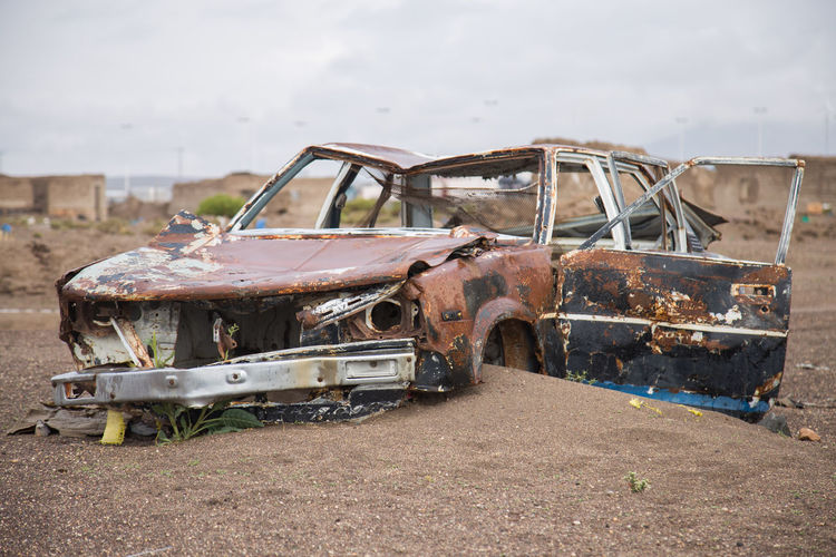Old Abandoned Car On Field Against Sky