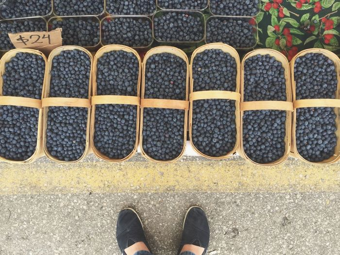 Low section of person wearing black shoes standing by blueberries in baskets at market stall