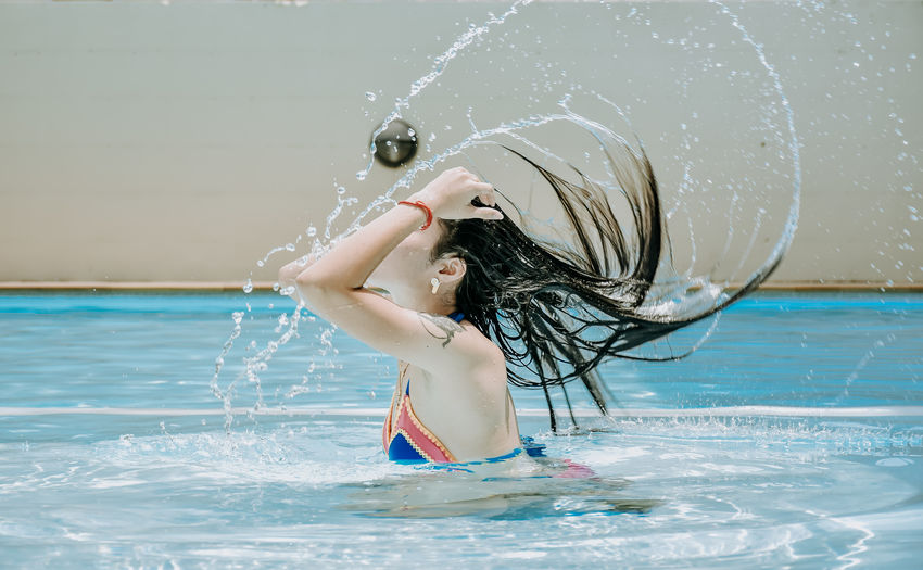 Young woman with arms raised in swimming pool