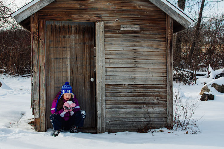 Girl eating snow against wooden cabin
