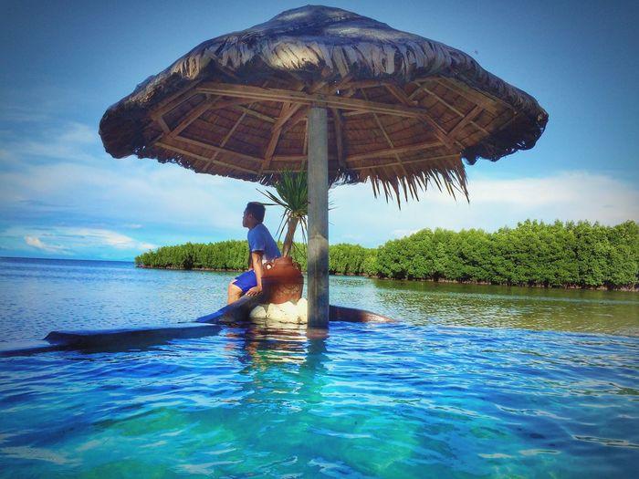 Side view of man sitting under parasol in lake