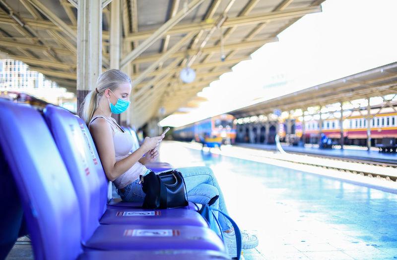 Side view of woman sitting on railway bridge