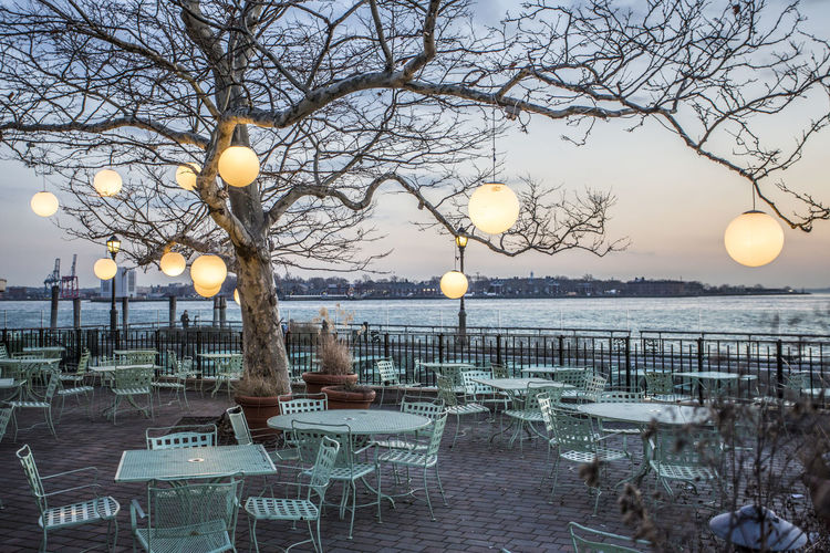 Empty chairs and tables against the river
