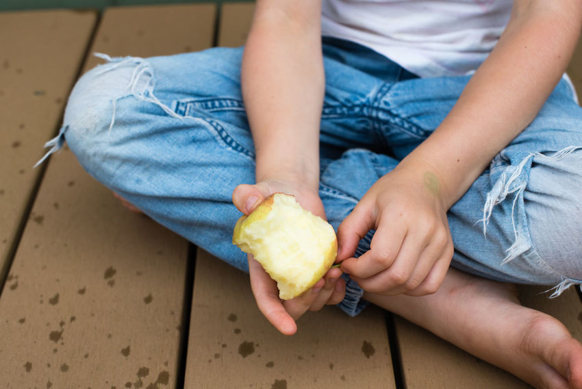 Apple Casual Clothing Child Childhood Focus On Foreground Food Food And Drink Freshness Fruit Hand Healthy Eating Holding Human Body Part Indoors  Jeans Lifestyles Midsection One Person Real People Sitting Wellbeing Women