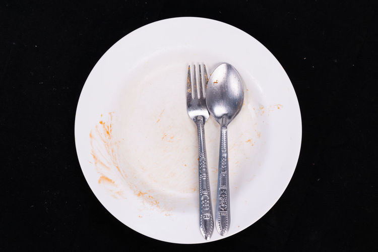 Empty plate with stain of food Spoon Black Background Crockery Dirty Eating Utensil Empty Plate Empty Plates, Food Food And Drink Fork High Angle View Indoors  Kitchen Utensil Leftovers No People Plate Stain Of Food Steel Still Life Studio Shot Table Knife White Color