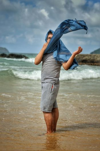 Man Wearing Scarf While Standing In Sea Against Sky
