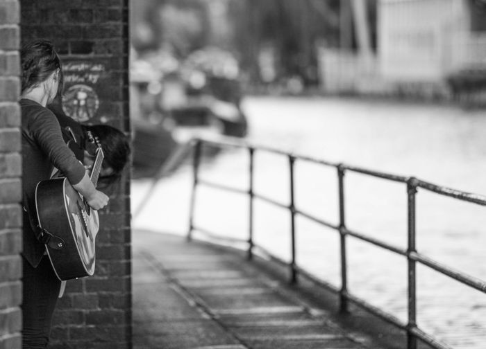 Woman playing guitar at footpath by river