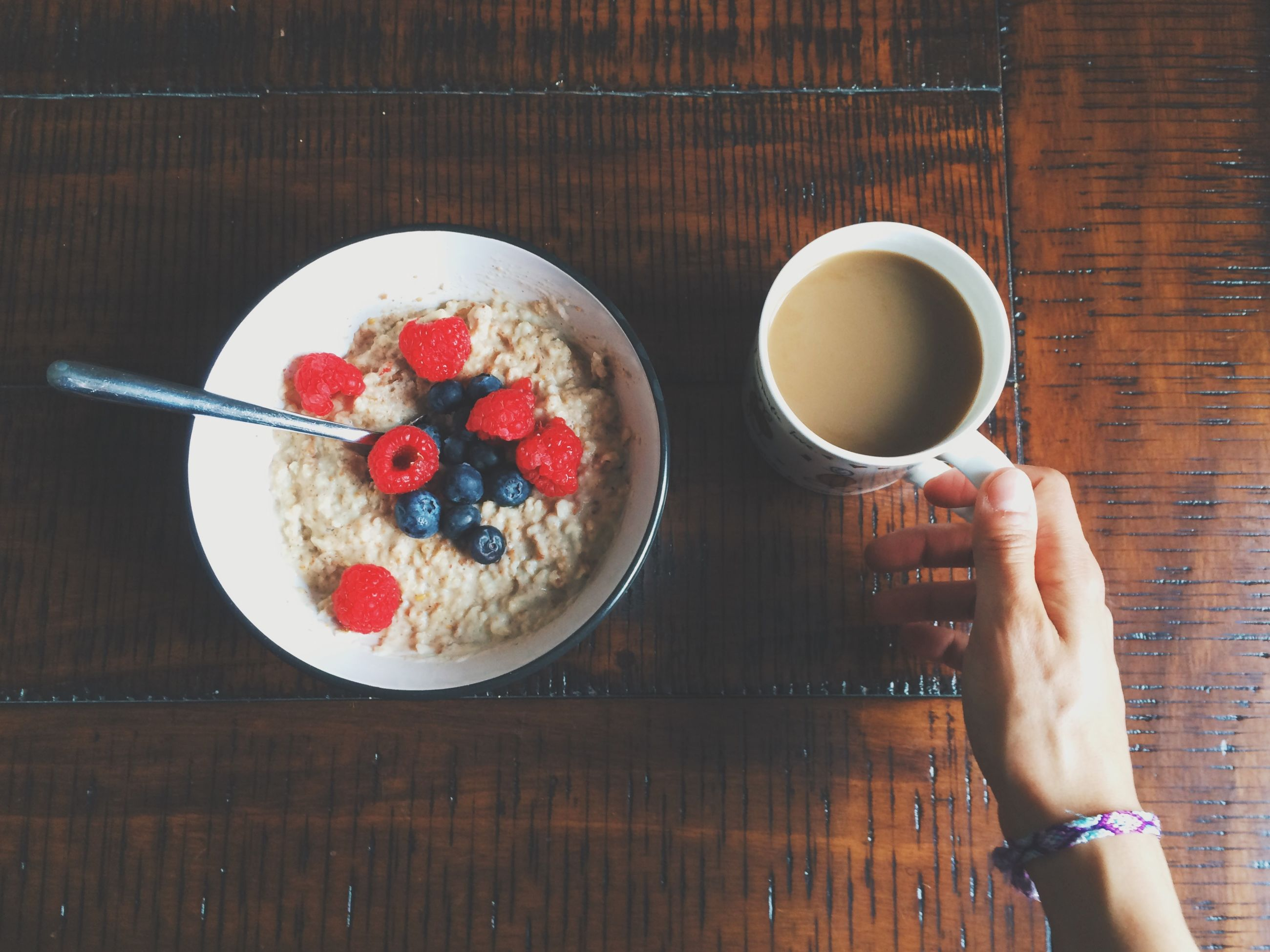 food and drink, freshness, person, food, holding, indoors, table, drink, refreshment, lifestyles, part of, coffee cup, fruit, healthy eating, sweet food, personal perspective