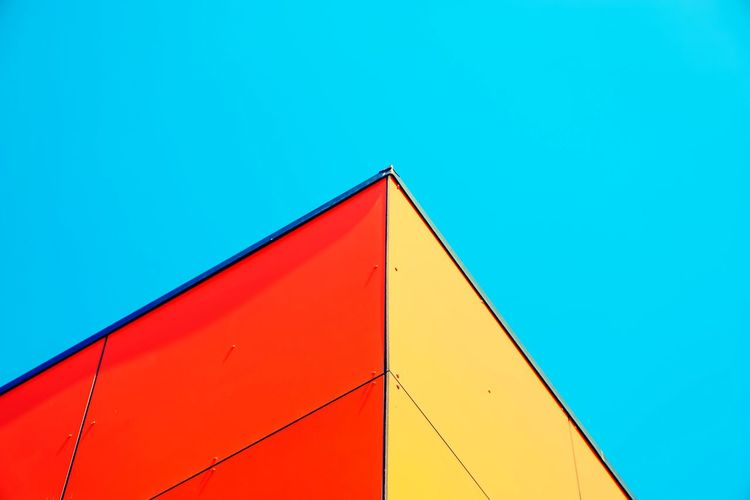 Low angle view of multi colored building against clear blue sky