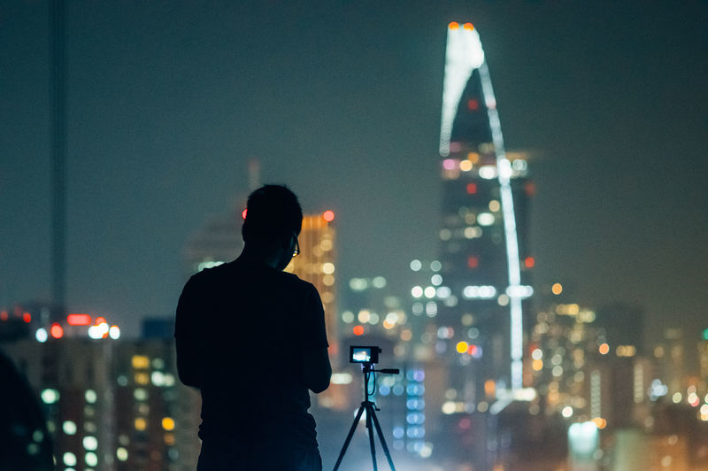 Silhouette man standing by digital camera on tripod against illuminated cityscape at night