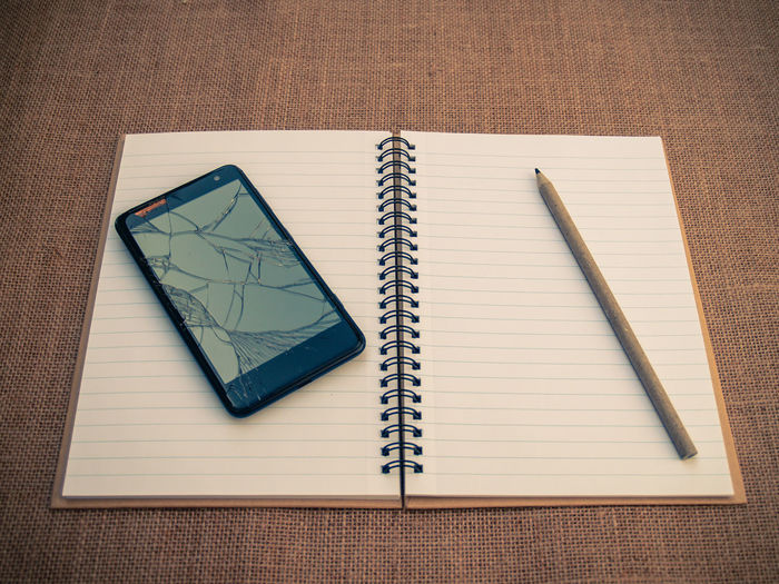 High angle view of smart phone with pencil and spiral notebook on table