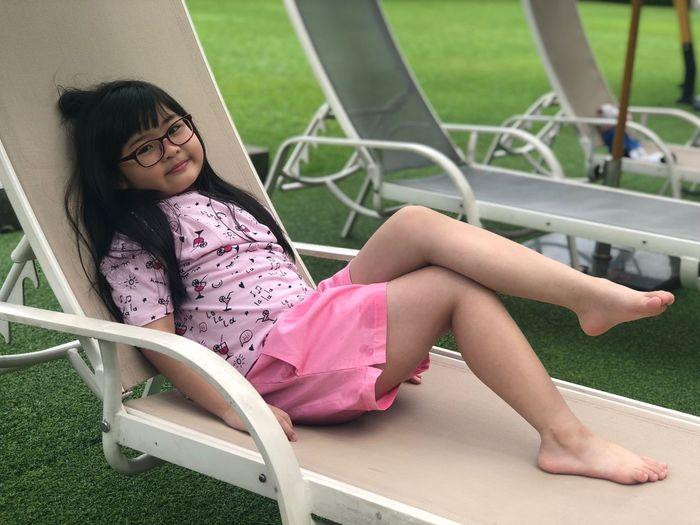 Full length of girl sitting on lounge chair