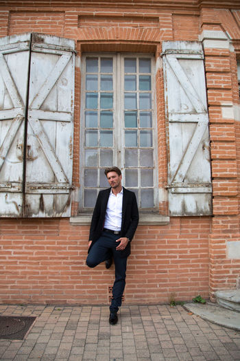 Full length portrait of handsome fashion model posing against old building