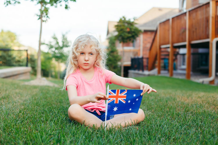 Cute girl with flag sitting on field