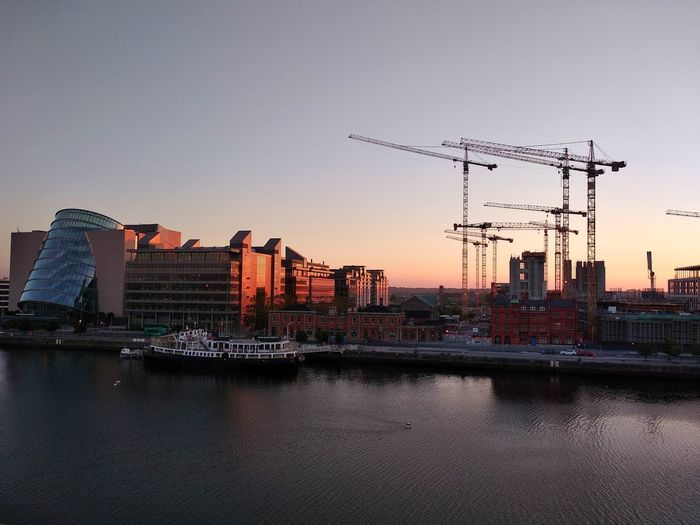 Pier over river by buildings against sky during sunset